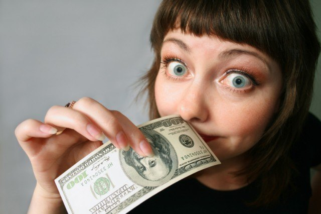 Woman holding $100 bill in front of face.