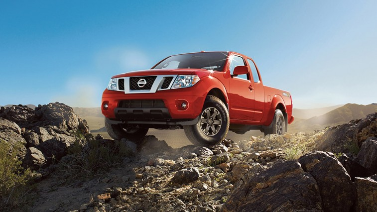 The 2015 Nissan Frontier shown in red on a rock mountain path