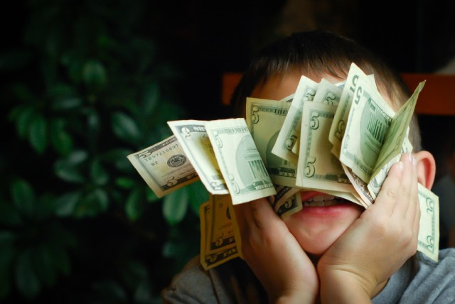 A kid holding his stash of money up to his face