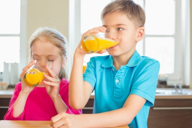 Siblings drinking orange juice in kitchen at home