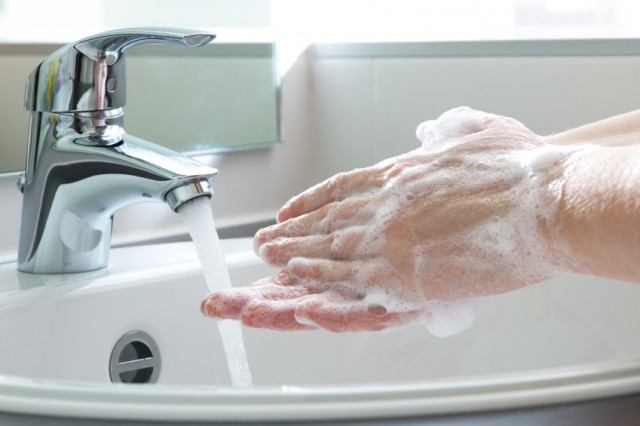 A person washes their hands