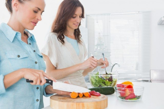 Two women are making a salad and cutting up vegetables at a kitchen counter.