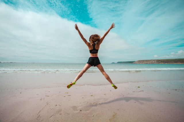 girl jumping at beach