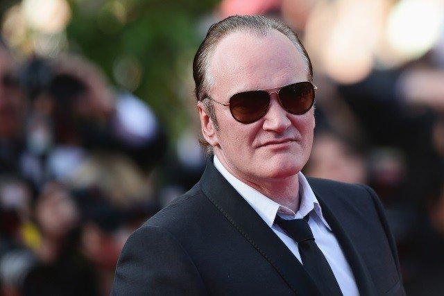 Quentin Tarantino wearing dark glasses and a suit and tie at a premiere.
