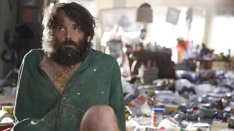 A bearded man sits on a messy floor in a green hoodie
