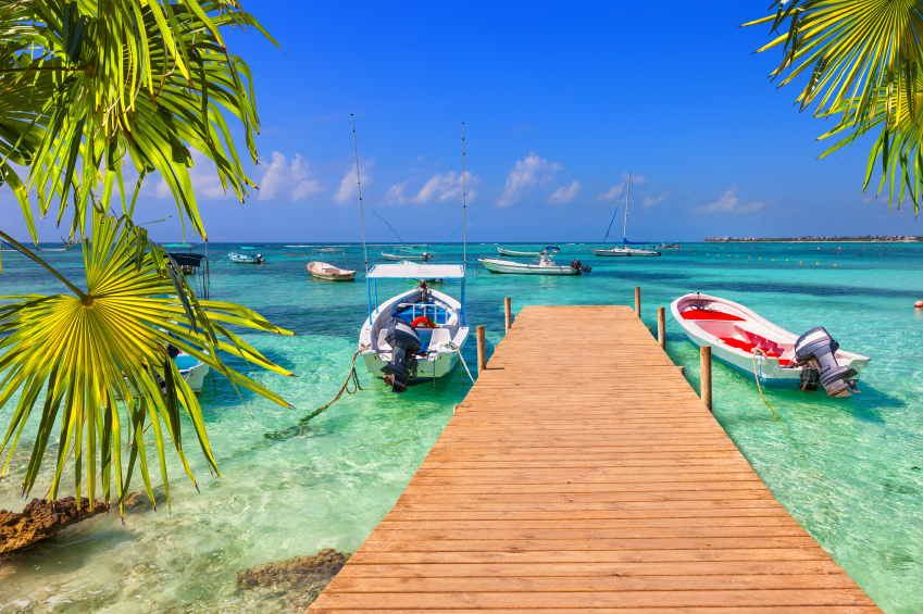 wooden pier and fishing boats on a Caribbean beach with transparent waters, beach