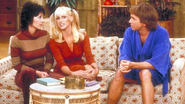 Joyce DeWitt, Suzanne Sommers, and Jhon Ritter sit together on a patterned couchinThree's Company