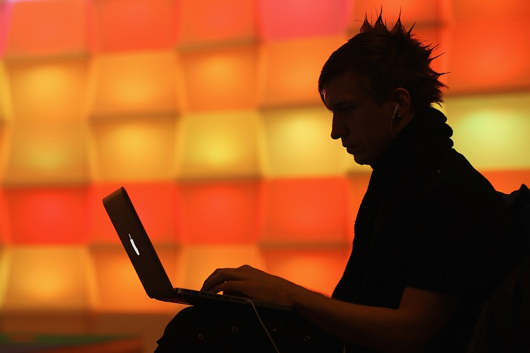 a hacker at a computer in front of orange squares