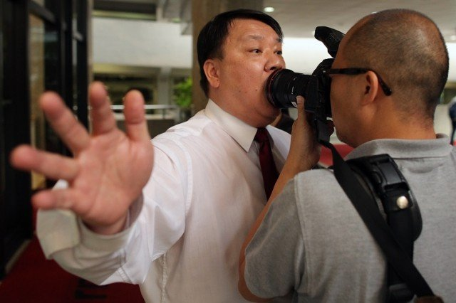 A security guard attempts to restrict a photographer from taking photos of a protest - Ed Jones/AFP/Getty Images