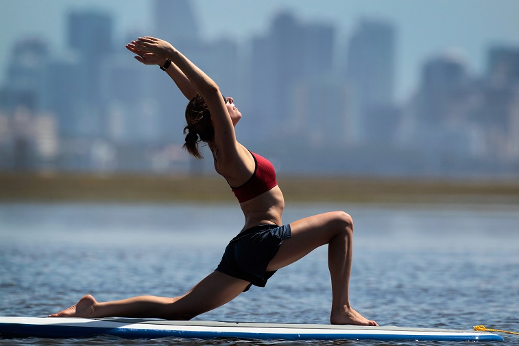 Yoga instructor Sarah Henry leads a class during a paddleboard yoga session - Source: Joe Raedle/Getty Images