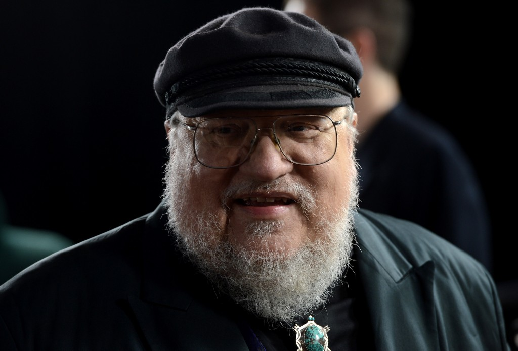 George R.R. Martin wearing a cap and glasses, and smiling