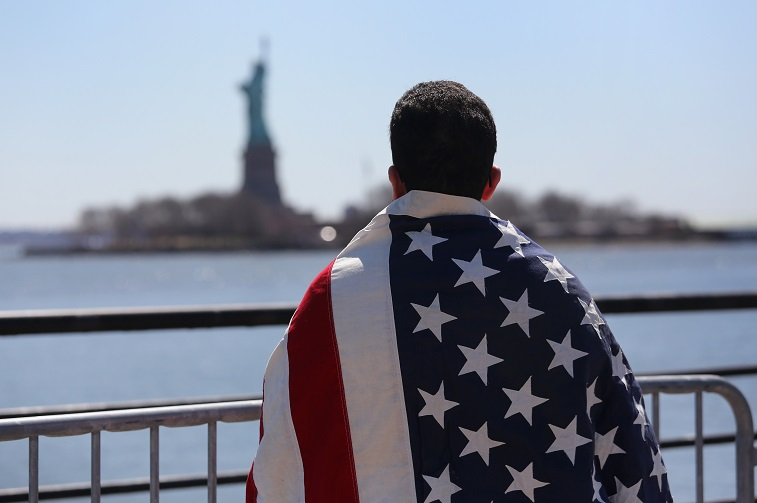 man wearing American flag looks toward statue of liberty