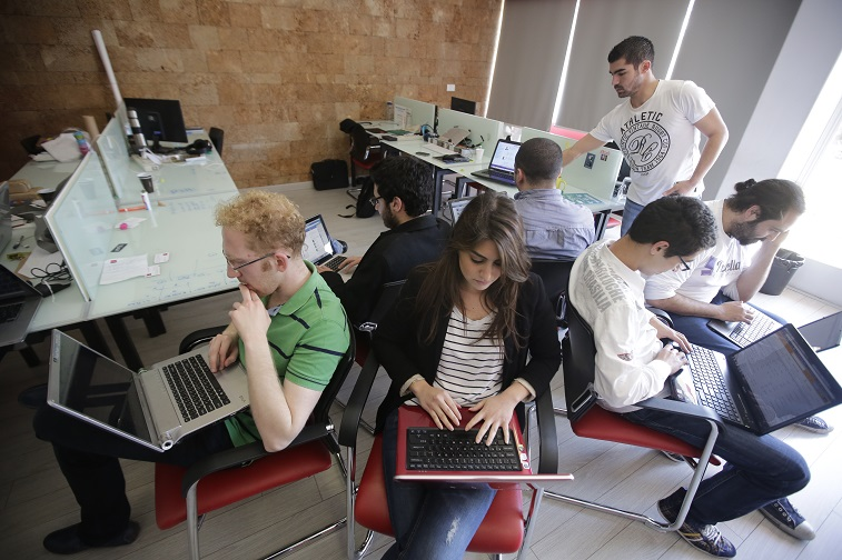 "entrepreneurs from different internet start-up companies work in the offices of ""accelerator"" Seeqnce in Beirut's Hamra district, on April 24, 2013. Lebanon, a country plagued for years by slow internet and crumbling infrastructure, is seeing a new interest in internet start-ups. Young Lebanese inspired by Western tales of start-up success, including Facebook, are taking advantage of projects intended to guide their budding businesses"