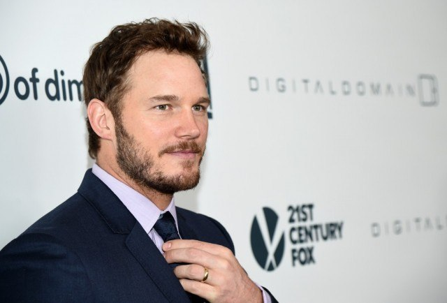 Chris Pratt adjusts his tie while poses for photos on a red carpet.