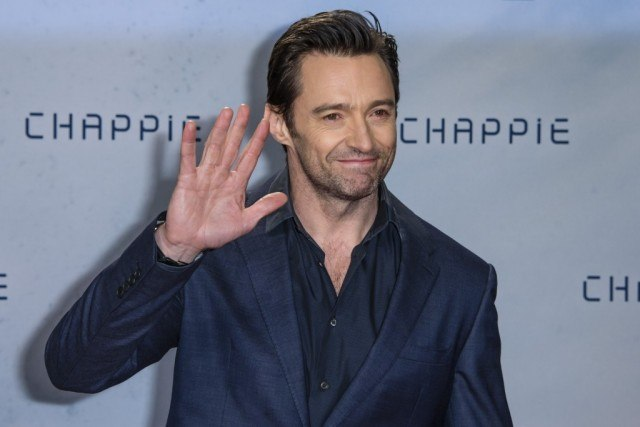 Hugh Jackman waves on the red carpet at the premiere of Chappie