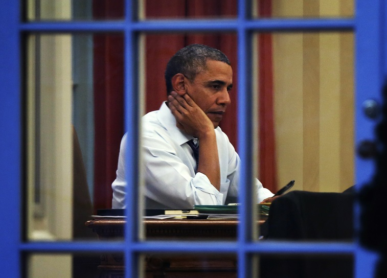 President Barack Obama, dealing with unrelenting stress and sleep loss, works in the Oval Office