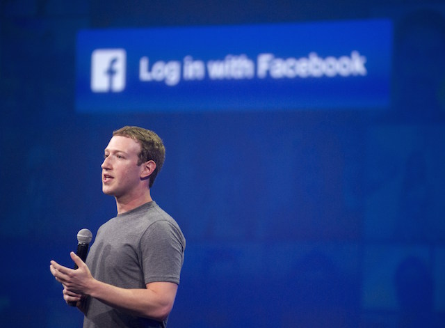 Mark Zuckerberg speaking in front of the Facebook logo
