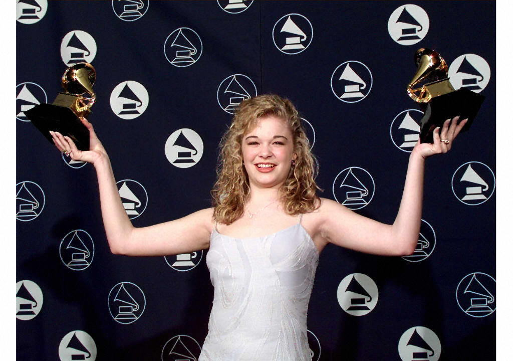LeAnn Rimes is holding up two Grammy awards on the red carpet.