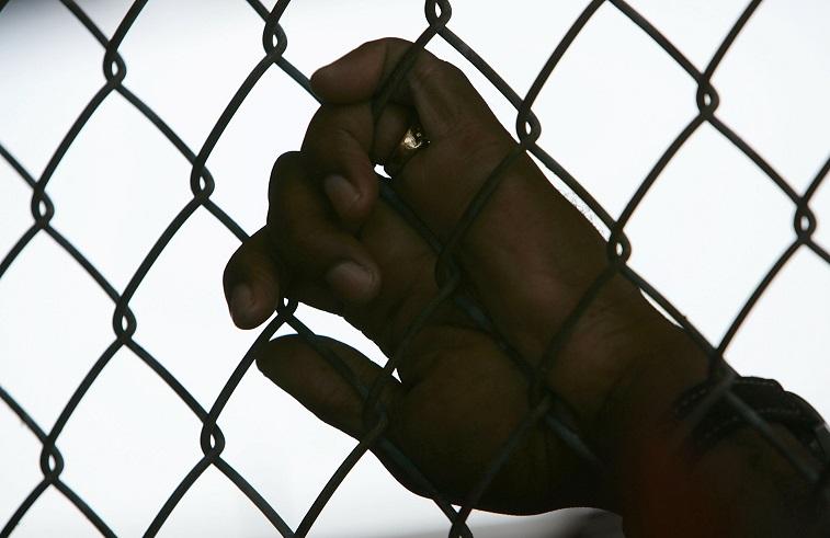 A prisoner holding a fence.