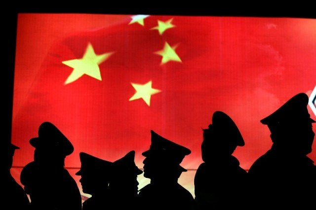 Security guard walk past the Chinese national flag - Source: China Photos/Getty Images