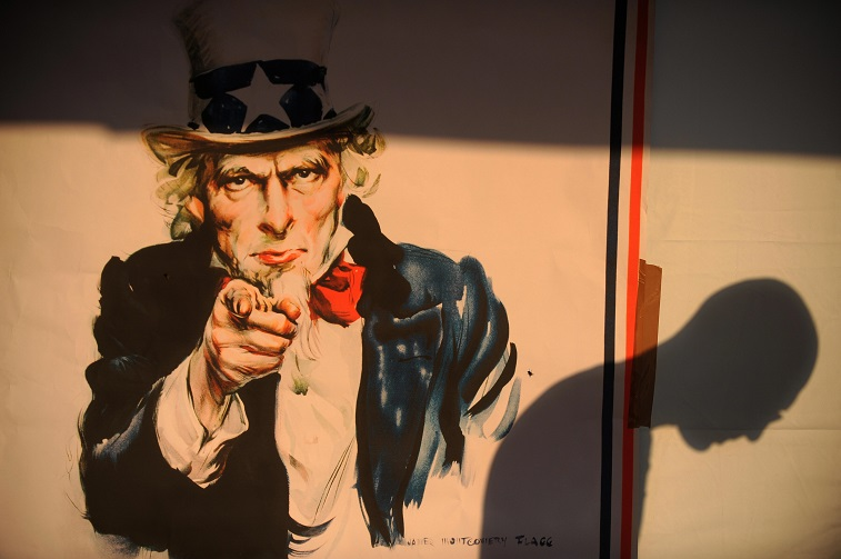 A shadow of a voter is seen on a poster of Uncle Sam