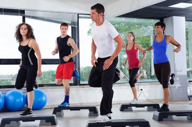 An aerobic class full of men and women getting a workout.