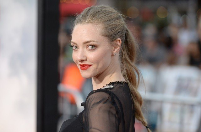 Amanda Seyfriend poses in a black outfit and ponytail on the red carpet.