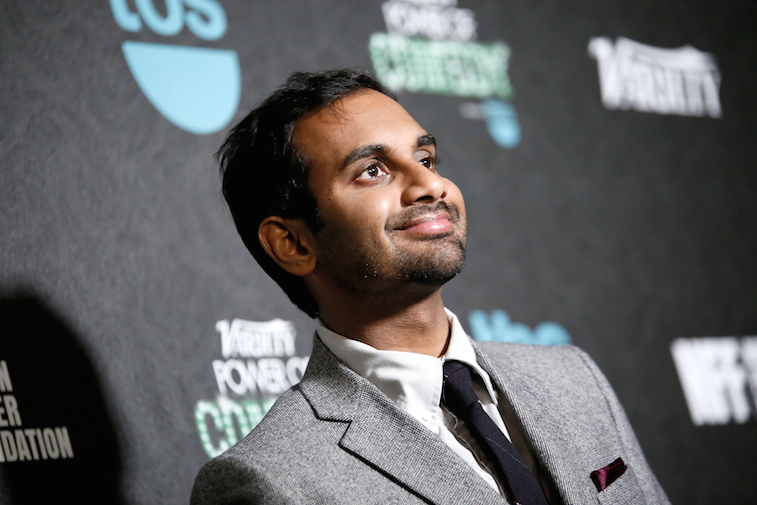 Aziz Ansari smiles in a grey tux