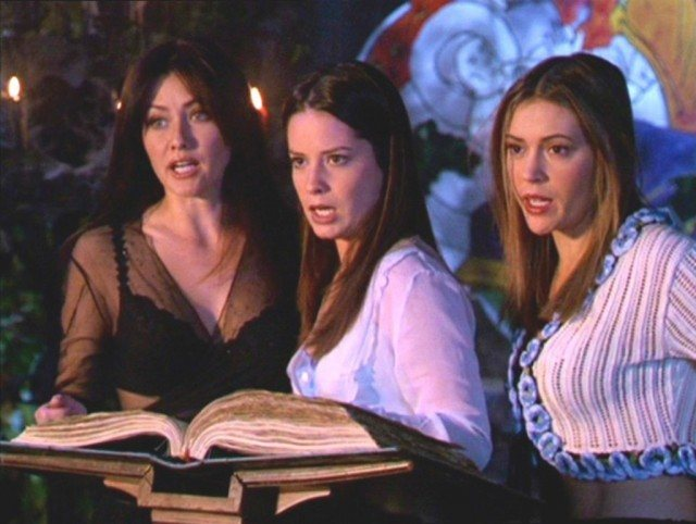 Shannon Doherty, Holly Marie Combs and Alyssa Milano look at a large book in Charmed