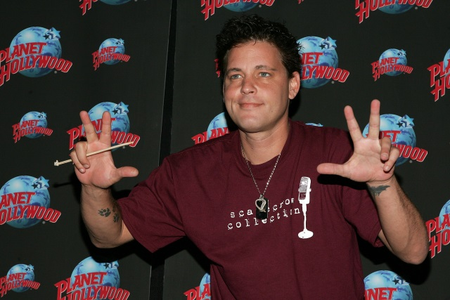 Corey Haim in a red tshirt, waving his hands in front of a Planet Hollywood wallpaper