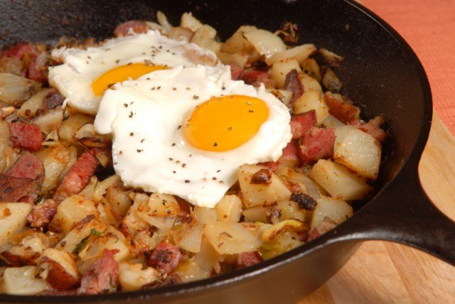 corned beef hash with two eggs in a skillet