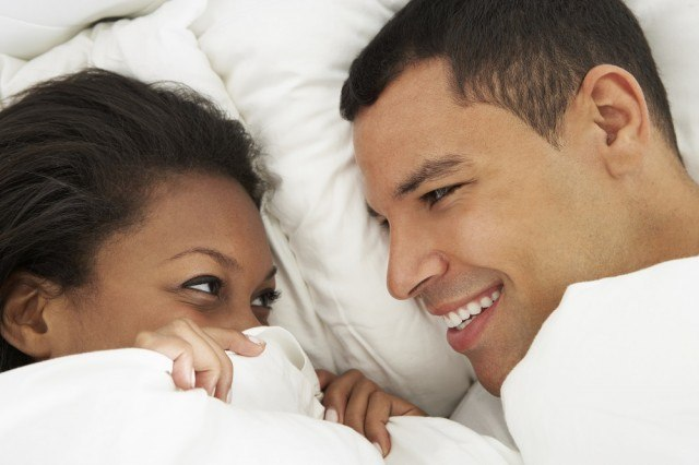 Man and woman lay cuddling on the bed