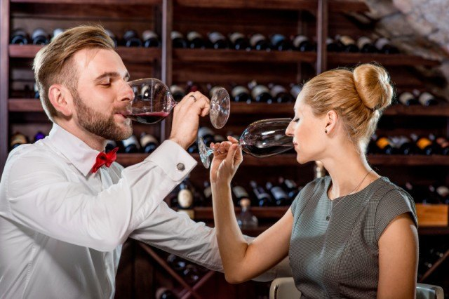 man and woman sipping wine in a wine cellar