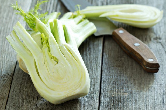 whole fennel bulb cut in half next to a knife on a wooden board