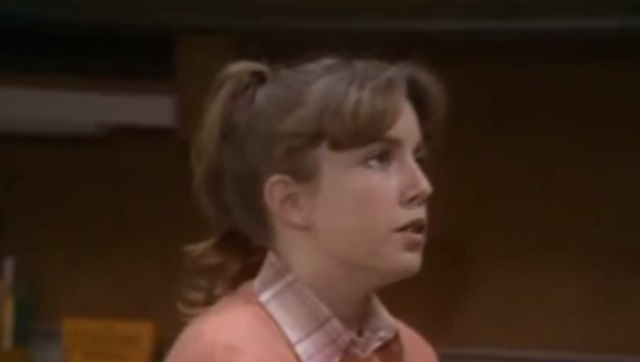 Dana Plato wearing a pink sweater, looking to the right of the frame
