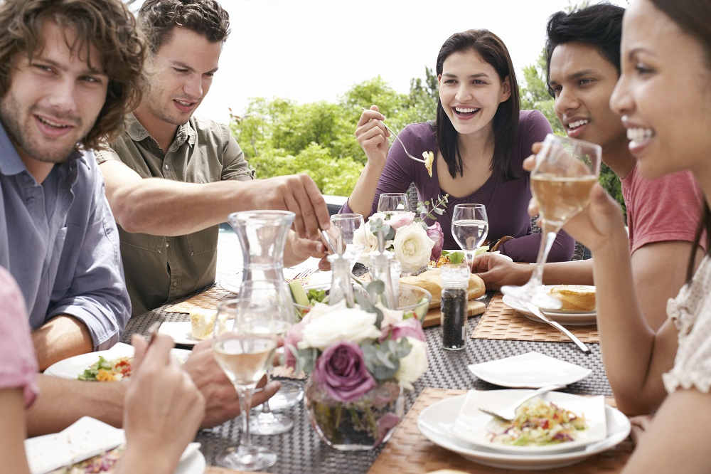 Group of friends sitting around dinner table outdoors