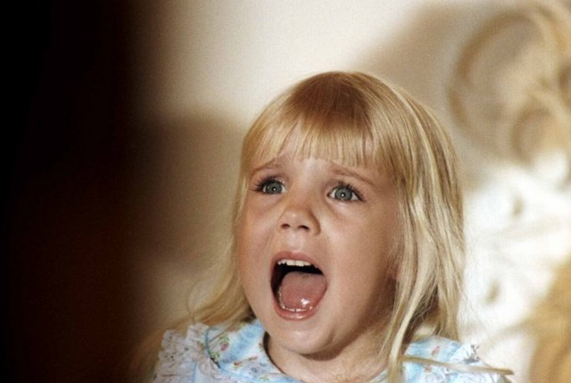 Heather O'Rourke in the movie Poltergeist, looking upward and screaming