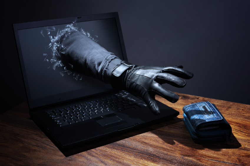 a hand with black glove coming through laptop scren to steal wallet