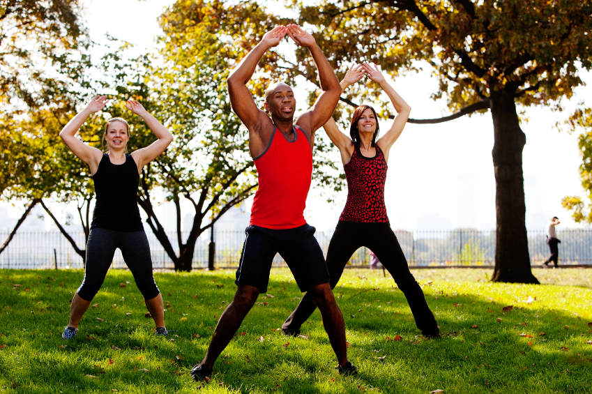 group of three people doing jumping jacks in the park on a beautiful day