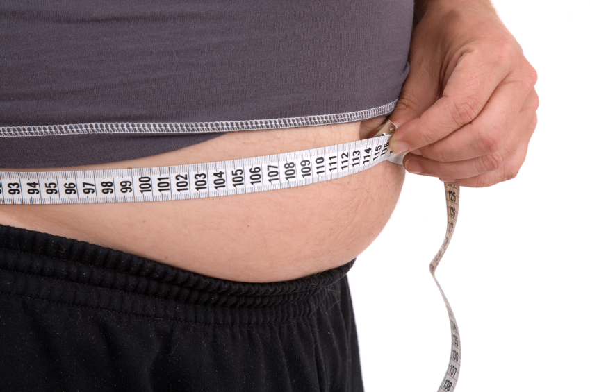 An obese man measures his waist