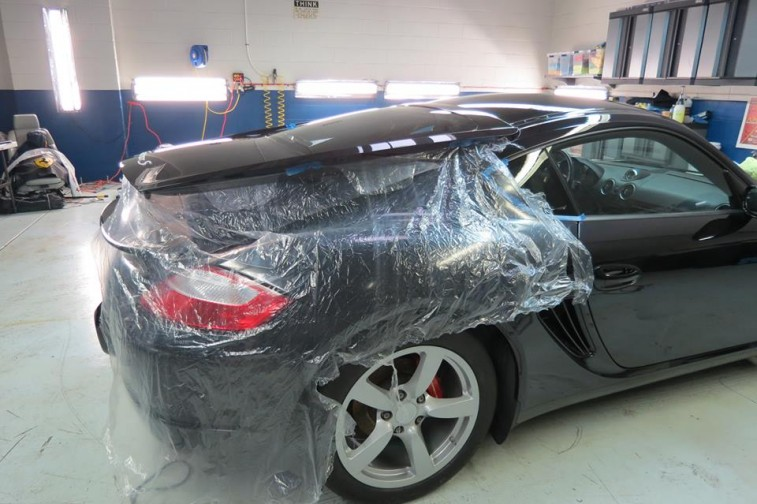 Car with sheet of plastic covering it