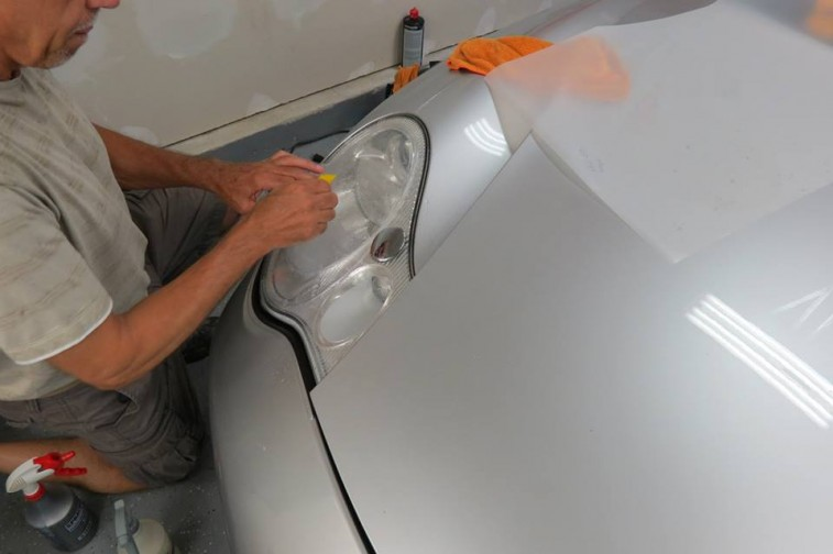 Man cleaning car headlight