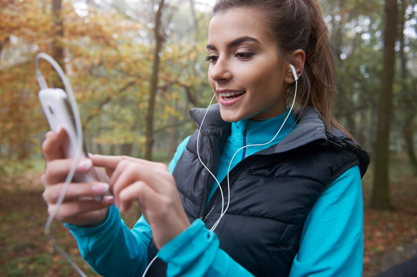 woman checking her phone and listening to music