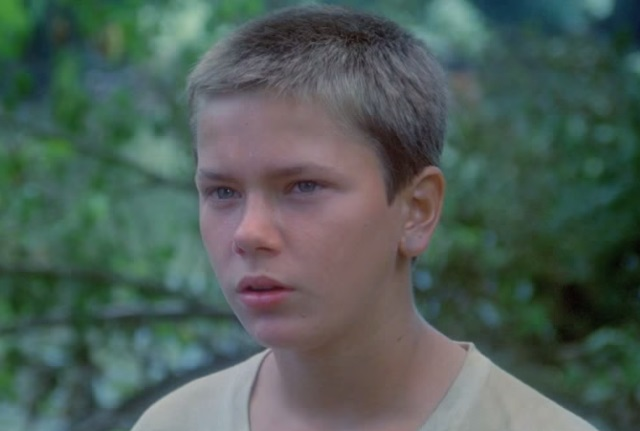 River Phoenix looks to his right in Stand By Me in the woods