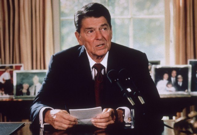 President Reagan sits in front of his desk holding note cards while speaking into a microphone.