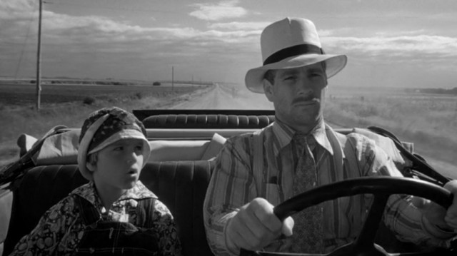 A young Tatum O'Neal sits in the passenger seat next to Ryan O'Neal in Paper Moon