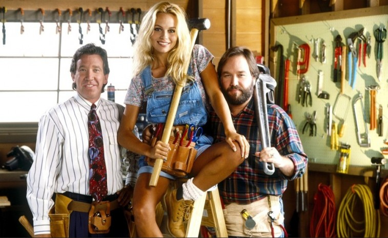 Tim Allen stands next to a woman and a man in a tool shop