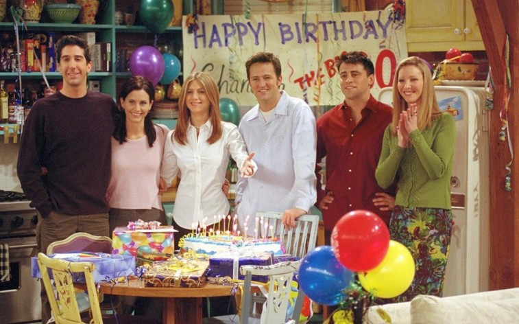 The cast of Friends stands around a table with a birthday cake