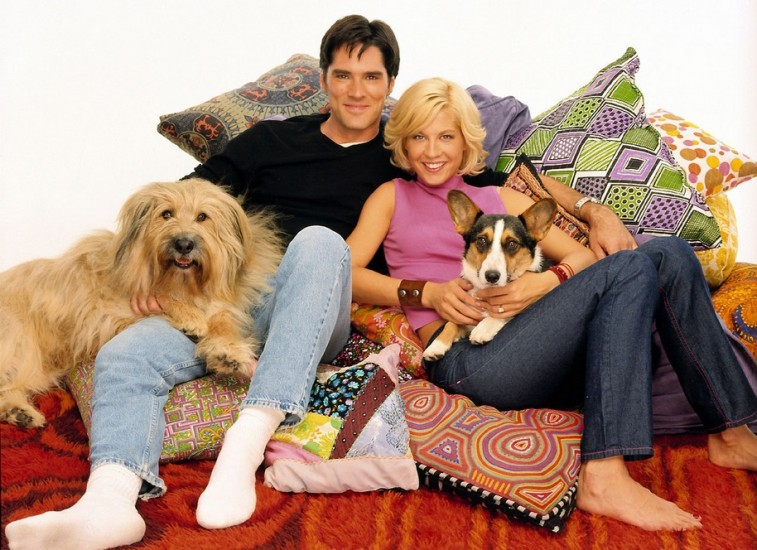 Dharma and Greg lay on a pile of pillows while holding their dogs in Dharma and Greg