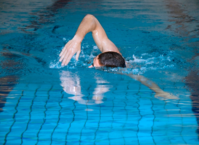 man swimming in an indoor pool